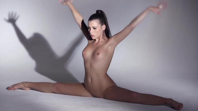 Naked brunette sits naked on a twine
